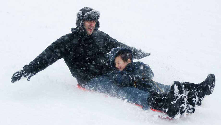 Julian Fischer and his son, Zavoli, 5, take advantage snow by sledding on a hill at Lyndale Farmstead, Sunday, Dec. 9, 2012, in Minneapolis. A major winter storm was expected to dump 9 to 15 inches across a broad belt of central Minnesota including the Twin Cities area by Sunday night, and the storm was also to bring heavy snow to parts of western Wisconsin. (AP Photo/The Star Tribune, Richard Tsong-Taatarii) MANDATORY CREDIT; ST. PAUL PIONEER PRESS OUT; MAGS OUT; TWIN CITIES TV OUT. Photo: Richard Tsong-Taatarii, Associated Press / The Star Tribune