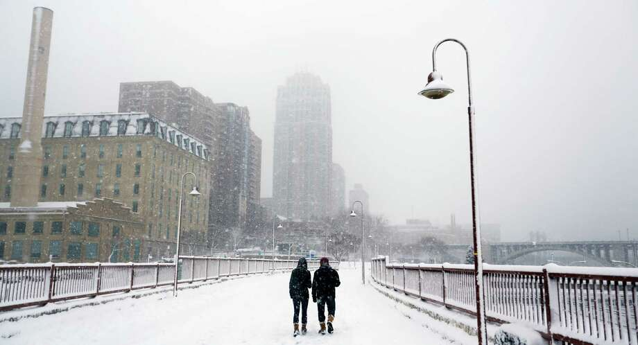 A couple walk in the snow on Sunday, Dec. 9, 2012, in Minneapolis. A major winter storm is expected to dump 9 to 15 inches across a broad belt of central Minnesota including the Twin Cities area by Sunday night, and the storm was also to bring heavy snow to parts of western Wisconsin. (AP Photo/The Star Tribune, Richard Tsong-Taatarii)  MANDATORY CREDIT; ST. PAUL PIONEER PRESS OUT; MAGS OUT; TWIN CITIES TV OUT Photo: Richard Tsong-Taatarii, Associated Press / The Star Tribune