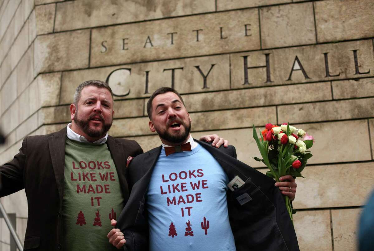 Keith Bacon, left, and his new husband Corianton Hale show off their T-shirts after the pair were married in Seattle City Hall on Sunday, December 9, 2012, the first day same-sex couples in Washington State can legally be married.