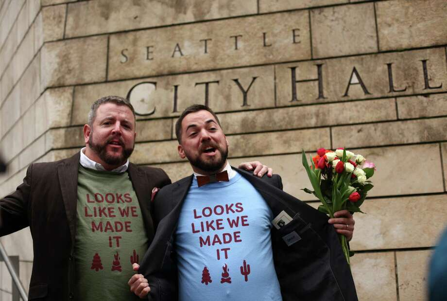 Keith Bacon, left, and his new husband Corianton Hale show off their T-shirts after the pair were married in Seattle City Hall. Photo: JOSHUA TRUJILLO / SEATTLEPI.COM
