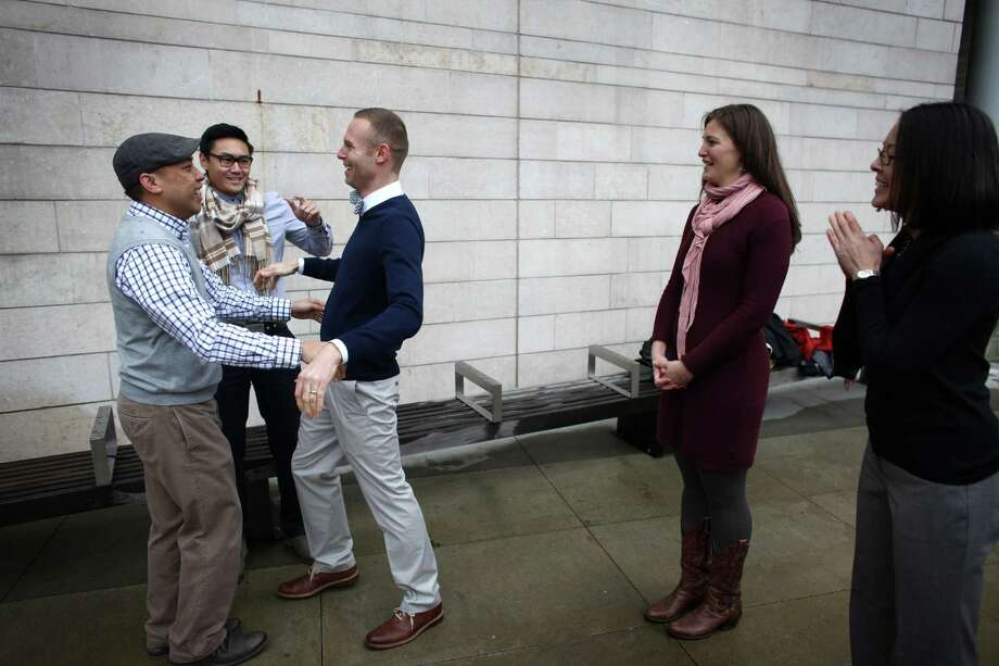 "Bernie Liang, left, and his husband Ryan Hamachek prepare to kiss as they are married by Paolo Campbell outside of Seattle City Hall. Liang and Hamachek tried to get a slot in the official City Hall weddings but were unable so they decided to just get married outside. ""We flash mobbed the wedding ceremonies,"" said Liang. They have been together for 8 years. At right are witnesses Megan Garner and Monica Nixon, far right. Photo: JOSHUA TRUJILLO / SEATTLEPI.COM"