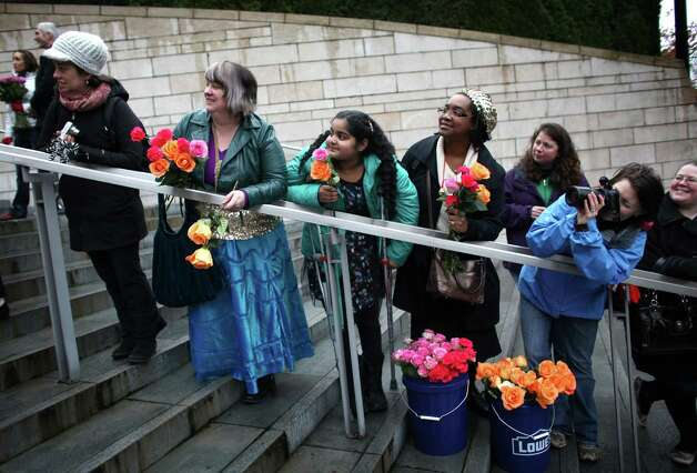 People watch as newly-married same-sex couples walk down the stairs of Seattle City Hall after they were married on Sunday, December 9, 2012, the first day same-sex couples in Washington State can legally be married. Photo: JOSHUA TRUJILLO / SEATTLEPI.COM