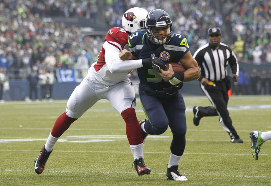 Seattle Seahawks quarterback Russell Wilson (3) is tackled by Arizona Cardinals outside linebacker Sam Acho (94) during the first quarter of an NFL football game in Seattle, Sunday, Dec. 9, 2012. Photo: AP
