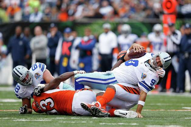 Michael Johnson #93 and Carlos Dunlap #96 of the Cincinnati Bengals combine to sack Tony Romo #9 of the Dallas Cowboys during the game at Paul Brown Stadium on December 9, 2012 in Cincinnati, Ohio. Photo: Joe Robbins, Getty Images / 2012 Getty Images