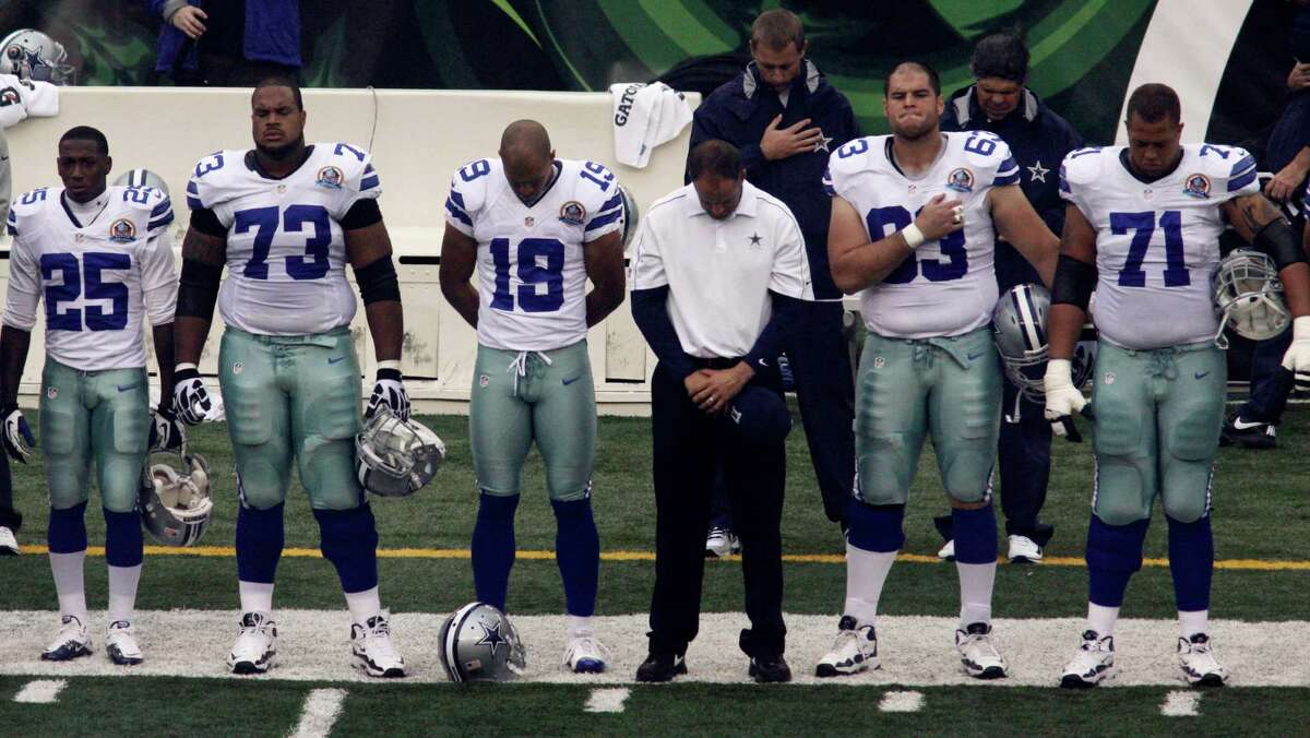Dallas Cowboys players hang their heads prior to an NFL football game against the Cincinnati Bengals, Sunday, Dec. 9, 2012, in Cincinnati, during a moment of silence honoring teammate Jerry Brown who was killed in an automobile accident. (AP Photo/Tom Uhlman)