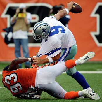 Dallas Cowboys quarterback Tony Romo (9) is sacked by Cincinnati Bengals defensive end Michael Johnson (93) in the first half of an NFL football game, Sunday, Dec. 9, 2012, in Cincinnati. (AP Photo/Michael Keating) Photo: Michael Keating, Associated Press / FR170759 AP