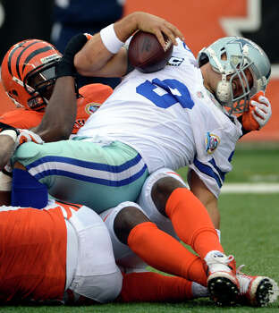 Dallas Cowboys quarterback Tony Romo (9) is sacked by Cincinnati Bengals defensive ends Carlos Dunlap and Michael Johnson in the first half of an NFL football game, Sunday, Dec. 9, 2012, in Cincinnati. (AP Photo/Michael Keating) Photo: Michael Keating, Associated Press / FR170759 AP