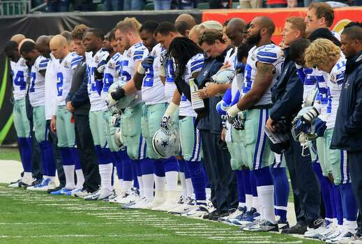 Dallas Cowboys players hang their heads during a moment of silence honoring teammate Jerry Brown who was killed in an automobile accident prior to an NFL football game against the Cincinnati Bengals, Sunday, Dec. 9, 2012, in Cincinnati. (AP Photo/Al Behrman) Photo: Al Behrman, Associated Press / AP