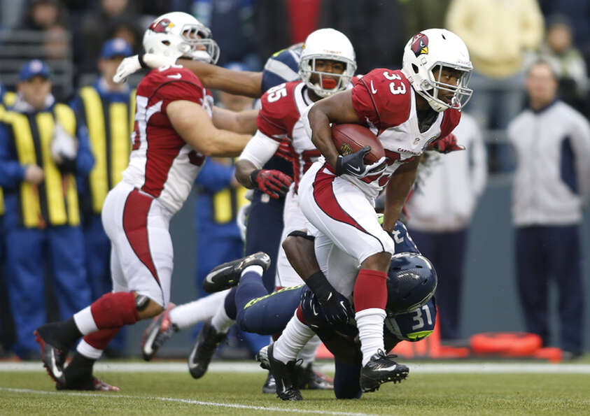 Arizona Cardinals running back William Powell (33) is tackled by Seattle Seahawks strong safety Kam