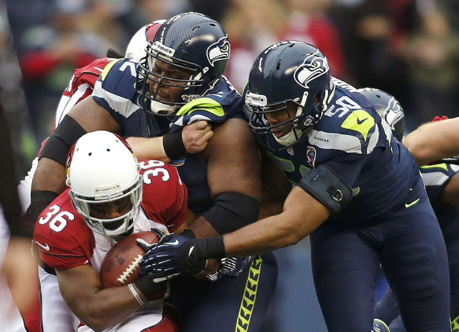 Seattle Seahawks defensive tackle Brandon Mebane (92) and outside linebacker K.J. Wright (50) tackle Arizona Cardinals running back LaRod Stephens-Howling (36) during the first quarter of an NFL football game in Seattle, Sunday, Dec. 9, 2012. Photo: AP