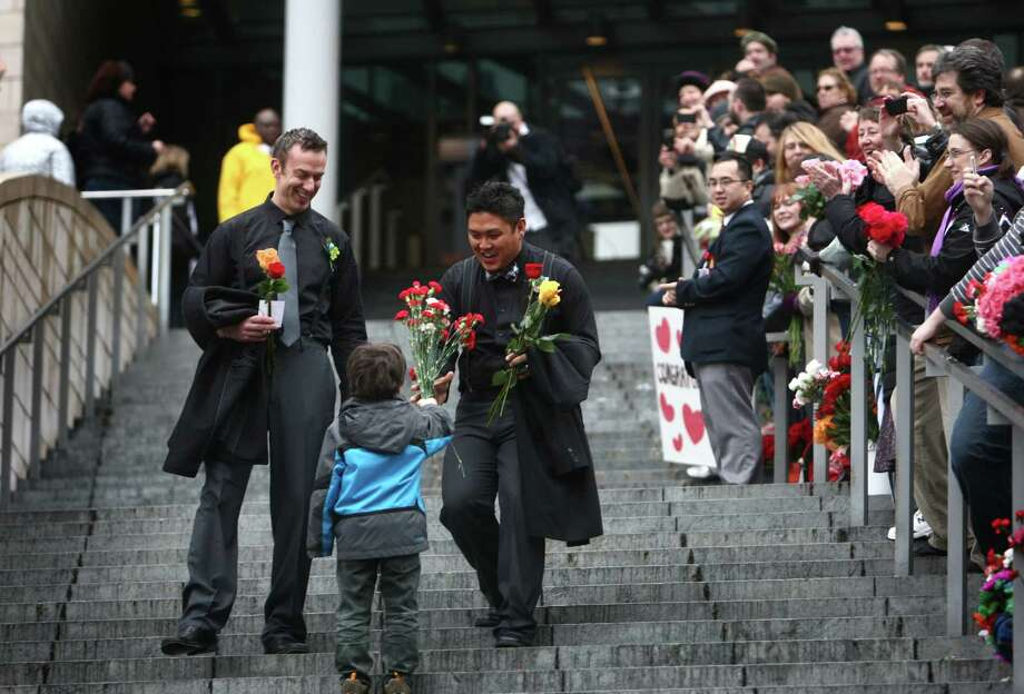 Luke Botzheim, left, and Allan Carandang are handed flowers  as they walk down the stairs of Seattle City Hall after they were married. Photo: JOSHUA TRUJILLO / SEATTLEPI.COM