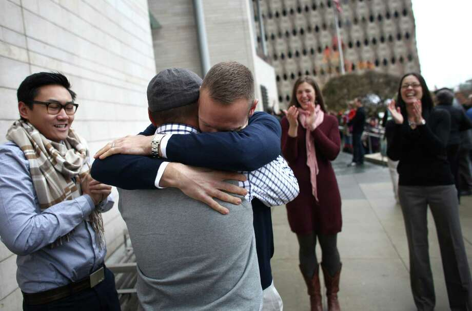 "Bernie Liang, left, and his husband Ryan Hamachek embrace after they were married by Paolo Campbell outside of Seattle City Hall. Liang and Hamachek tried to get a slot in the official City Hall weddings but did not so they decided to just get married outside. ""We flash mobbed the wedding ceremonies,"" said Liang. At right are witnesses Megan Garner and Monica Nixon, far right. Photo: JOSHUA TRUJILLO / SEATTLEPI.COM"