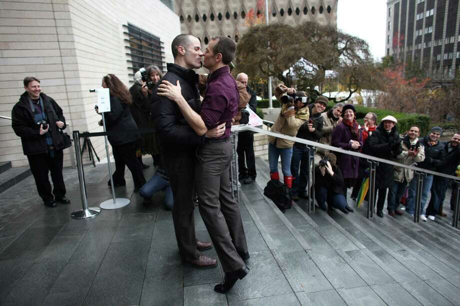 A newly-married couple kisses as they walk down the stairs of Seattle City Hall after they were married. Photo: JOSHUA TRUJILLO / SEATTLEPI.COM