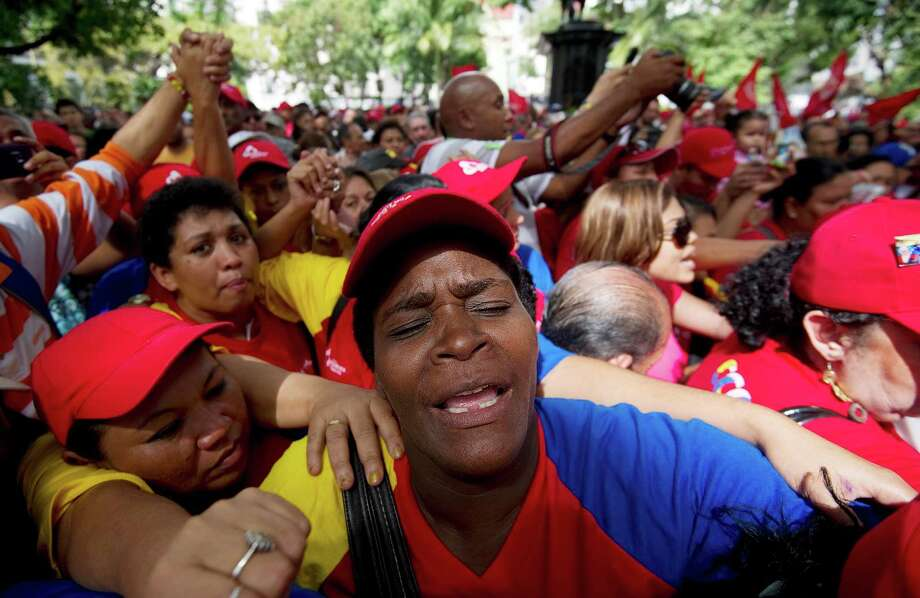 """Supporters of Venezuela's President Hugo Chavez rally in Caracas on December 9, 2012. Leftist President Chavez admitted a relapse of his cancer late Saturday and designated vice president Nicolas Maduro as his heir apparent in case """"something happened"""" to him.    AFP  PHOTO/JUAN BARRETOJUAN BARRETO/AFP/Getty Images Photo: JUAN BARRETO, AFP/Getty Images / AFP"""