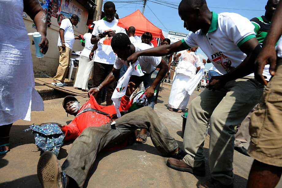 Supporters of the ruling party help a man in Accra who fell while celebrating the president's imminent victory in the election after snafus forced officials to extend voting by a day. Photo: Pius Utomi Ekpei, AFP/Getty Images