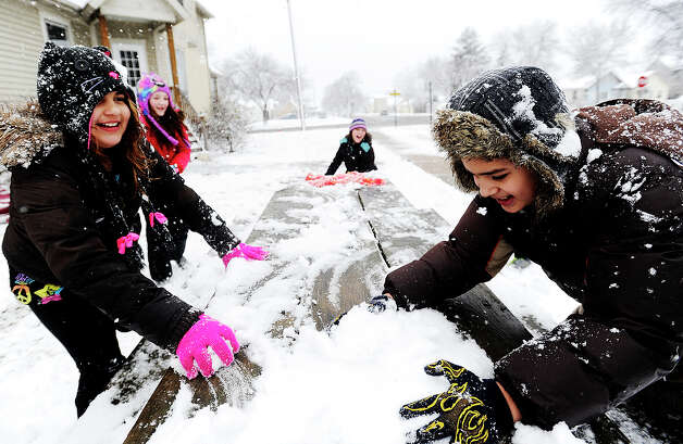 Chelsea Gerth, left, 9, and Angel Martinez Carbaja, 10, race to grab snow from a picnic table during a snowball fight in the fresh snow, Sunday, Dec. 9, 2012, in Winona, Minn. Around three inches of snow had fallen by noon on Sunday, according to the National Weather Service. (AP Photo/Winona Daily News, Joe Ahlquist) Photo: Joe Ahlquist, Associated Press / Winona Daily News