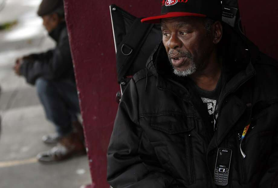 William Locke of San Francisco, who uses a wheelchair, wears his cell phone around his neck and says he could really use the money he would save with a low-cost or free cell phone plan. Photo: Carlos Avila Gonzalez, The Chronicle