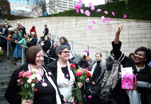 Robin Wyss, left, and Danielle Wyss are showered with rose petals as they walk down the stairs of Seattle City Hall after they were married on Sunday, December 9, 2012, the first day same-sex couples in Washington State can legally be married. Photo: JOSHUA TRUJILLO / SEATTLEPI.COM