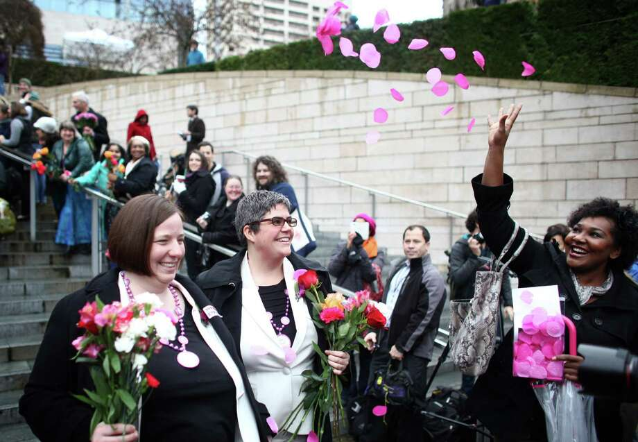 Robin Wyss, left, and Danielle Wyss are showered with rose petals as they walk down the stairs of Seattle City Hall after they were married. Photo: JOSHUA TRUJILLO / SEATTLEPI.COM