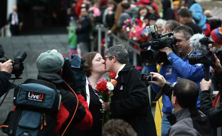 Robin Wyss, left, and Danielle Wyss kiss as they walk down the stairs of Seattle City Hall after they were married. Photo: JOSHUA TRUJILLO / SEATTLEPI.COM