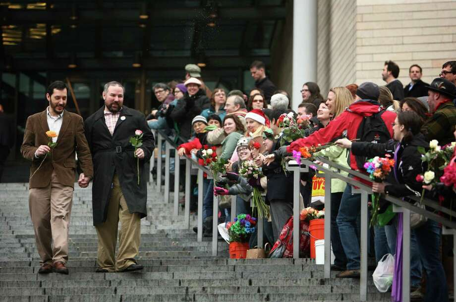 A newly-married couple is handed flowers as they walk down the stairs of Seattle City Hall. Photo: JOSHUA TRUJILLO / SEATTLEPI.COM