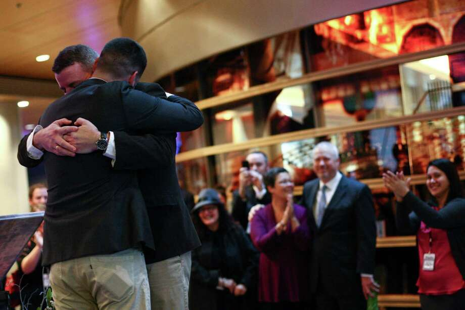 Corianton Hale, left and Keith Bacon embrace as they are married in Seattle City Hall. Photo: JOSHUA TRUJILLO / SEATTLEPI.COM