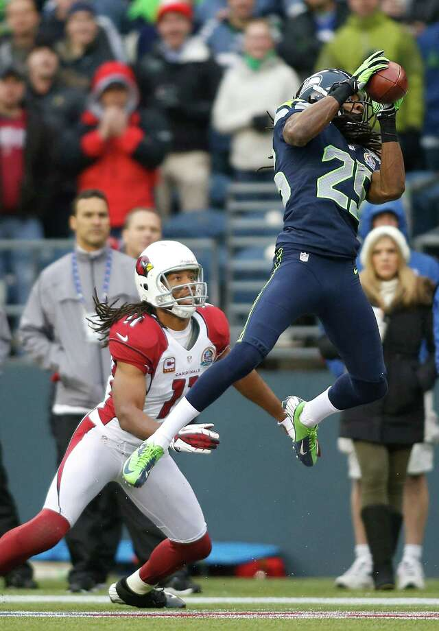 Seattle Seahawks cornerback Richard Sherman (25) intercepts a pass in front of Arizona Cardinals wide receiver Larry Fitzgerald (11) which was returned for a touchdown during the second quarter of an NFL football game in Seattle, Sunday, Dec. 9, 2012. Photo: AP