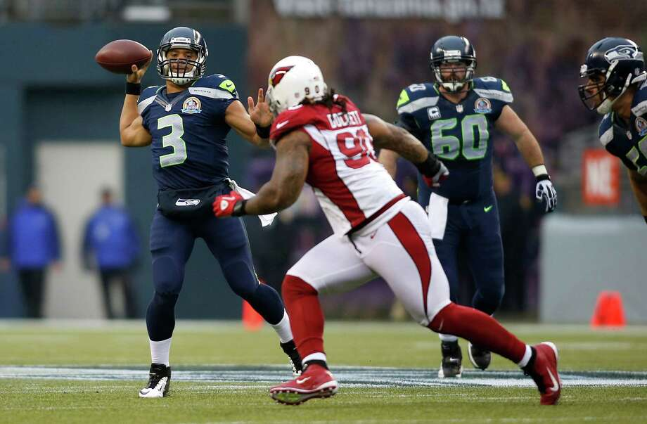 Seattle Seahawks quarterback Russell Wilson (3) passes as Arizona Cardinals defensive end Darnell Dockett (90) applies pressure during the first half of an NFL football game in Seattle, Sunday, Dec. 9, 2012. Photo: AP