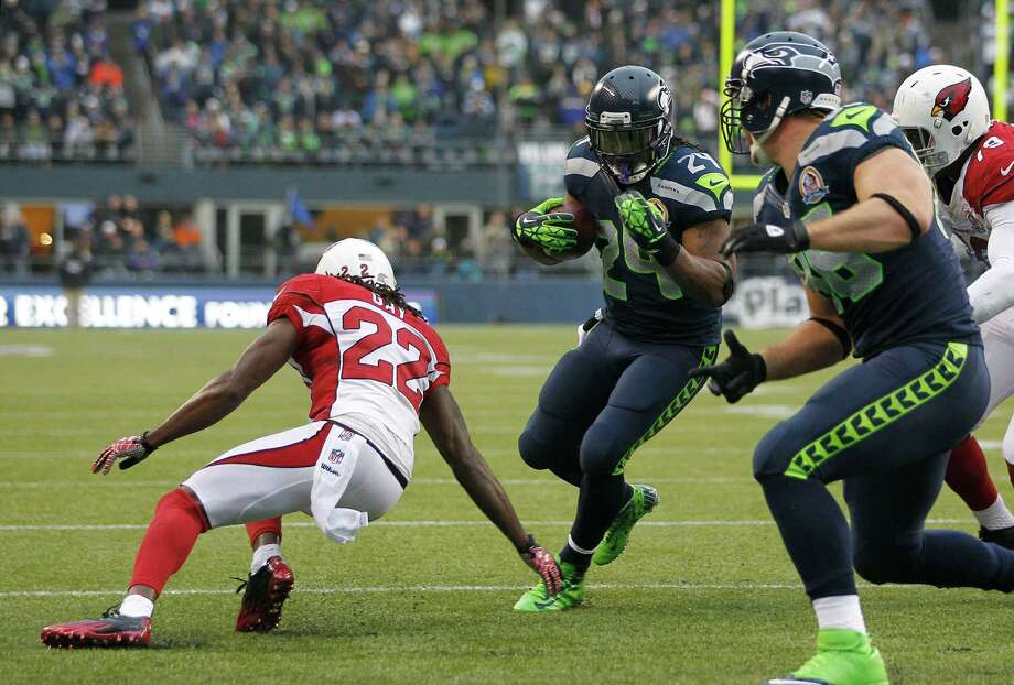 Seattle Seahawks running back Marshawn Lynch (24) scores on a 4-yard touchdown run against Arizona Cardinals cornerback William Gay (22) during the second quarter of an NFL football game in Seattle, Sunday, Dec. 9, 2012. Photo: AP