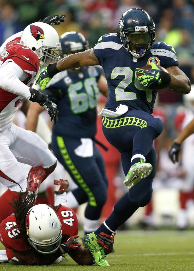 Seattle Seahawks running back Marshawn Lynch (24) runs for a 33-yard touchdown past Arizona Cardinals strong safety Rashad Johnson (49) and inside linebacker Daryl Washington (58) during the third quarterof an NFL football game in Seattle, Sunday, Dec. 9, 2012. Photo: AP