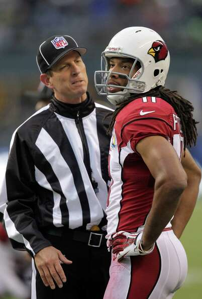 Arizona Cardinals wide receiver Larry Fitzgerald (11) talks with back judge Todd Prukop (30) during