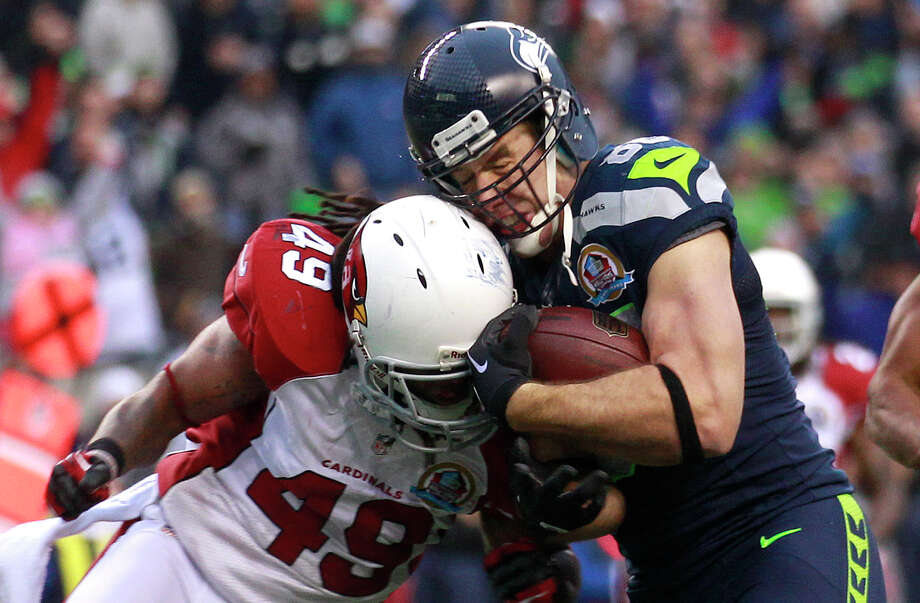 Seattle Seahawks tight end Zach Miller (86) is hit by Arizona Cardinals strong safety Rashad Johnson (49) as he scores on a 24-yard touchdown reception during the second quarter of an NFL football game in Seattle, Sunday, Dec. 9, 2012. Photo: AP