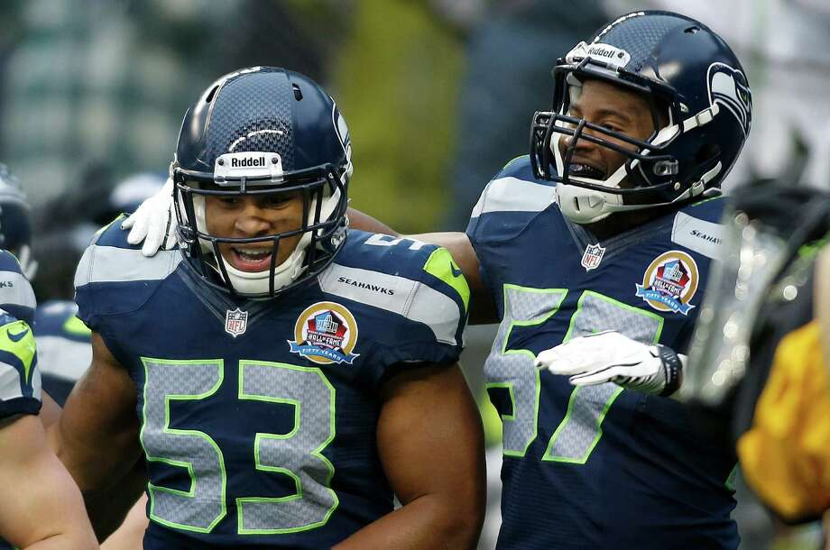 Seattle Seahawks linebacker Malcolm Smith (53) celebrates with linebacker Mike Morgan (57) after scoring a touchdown on a fumble recovery against the Arizona Cardinals during the second quarter of an NFL football game in Seattle, Sunday, Dec. 9, 2012. Photo: AP