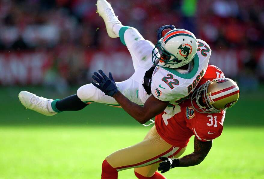 Miami Dolphins running back Reggie Bush, left, is stopped with the ball by San Francisco 49ers stron