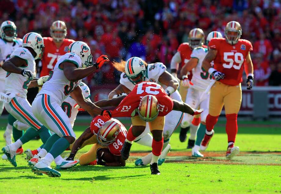 Running back Frank Gore (21) breaks a tackle for Wide receiver Randy Moss (84) during the first half of the San Francisco 49ers game against the Miami Dolphins at Candlestick Park in San Francisco, Calif., on Sunday December 9, 2012. Photo: Brant Ward, The Chronicle / ONLINE_YES
