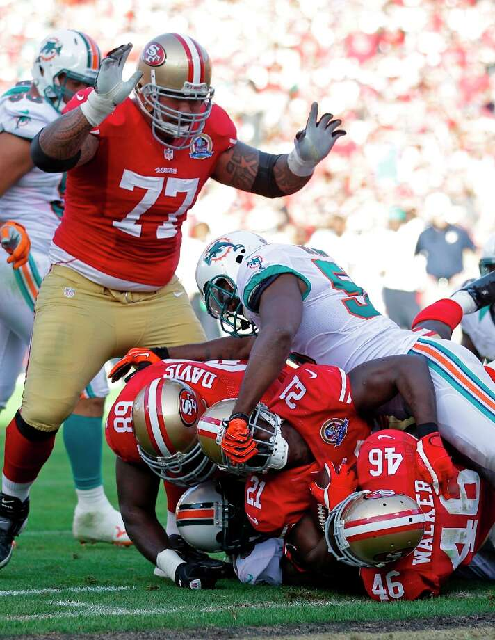 San Francisco 49ers guard Mike Iupati (77) celebrates as running back Frank Gore (21) carries the ball into the end zone for a touchdown on a one-yard run during the third quarter of an NFL football game against the Miami Dolphins in San Francisco, Sunday, Dec. 9, 2012. Also shown are San Francisco 49ers guard Leonard Davis (68) and 49ers tight end Delanie Walker (46). Photo: Marcio Jose Sanchez, Associated Press / AP
