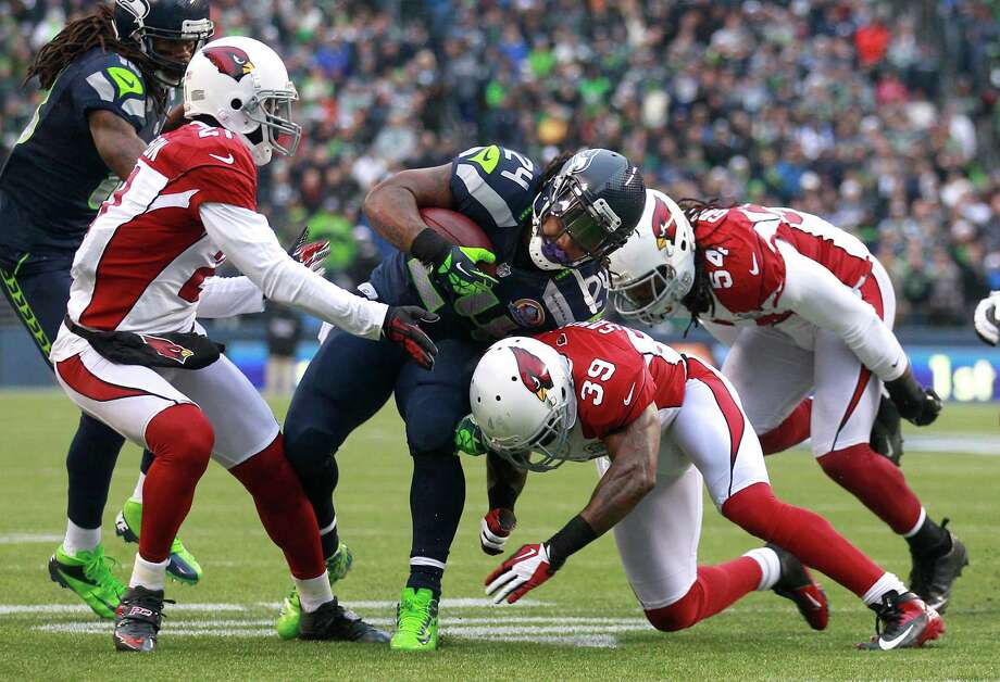 Seattle Seahawks running back Marshawn Lynch (24) runs against Arizona Cardinals cornerback Patrick Peterson (21), defensive back James Sanders (39), and outside linebacker Quentin Groves (54) of an NFL football game in Seattle, Sunday, Dec. 9, 2012. Photo: AP