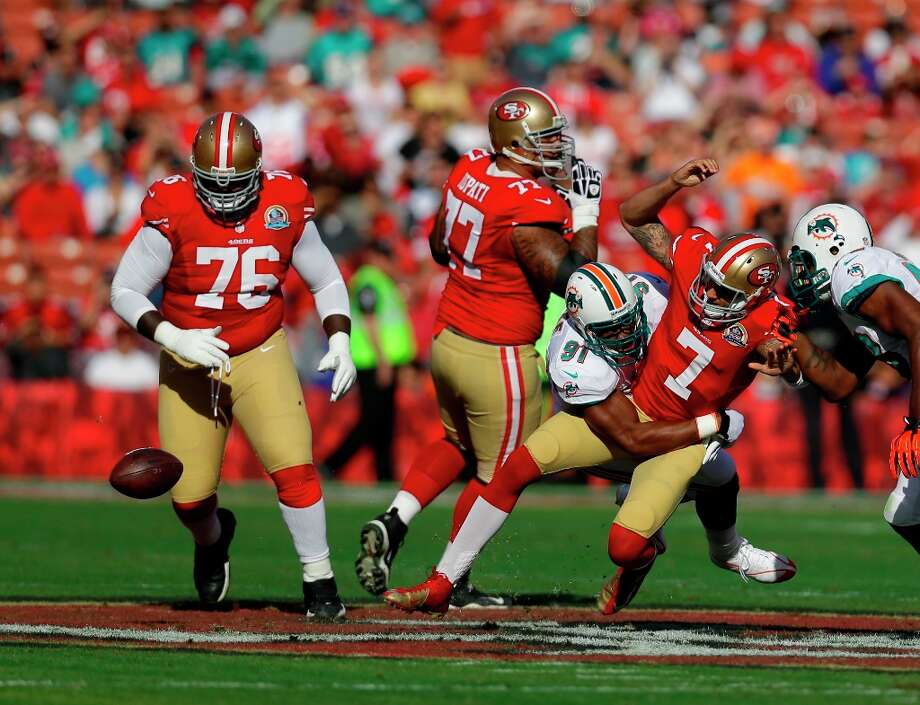 San Francisco 49ers quarterback Colin Kaepernick (7) is hit by Miami Dolphins defensive end Cameron Wake (91) after losing control of the ball during the first quarter of an NFL football game in San Francisco, Sunday, Dec. 9, 2012. Looking on is San Francisco 49ers tackle Anthony Davis (76) and guard Mike Iupati (77). Photo: Marcio Jose Sanchez, Associated Press / AP