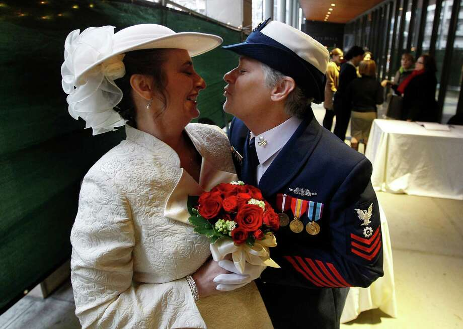 Retired U.S. Coast Guard Petty Officer 1st Class Nancy Monahan, right, wears her dress uniform as she leans to kiss her soon-to-be bride Deb Needham while they wait at Seattle City Hall to become among the first gay couples to legally wed in Washington state, Sunday, Dec. 9, 2012, in Seattle. The couple is from Renton, Wash. Gov. Chris Gregoire signed a voter-approved law legalizing gay marriage Dec. 5 and weddings for gay and lesbian couples began in Washington on Sunday, following the three-day waiting period after marriage licenses were issued earlier in the week. (AP Photo/Elaine Thompson) Photo: Elaine Thompson, STF / AP