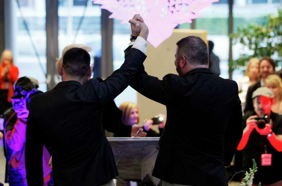 Newlyweds Corianton Hale, left, and Keith Bacon raise their arms in celebration after marrying at Seattle City Hall, Sunday, Dec. 9, 2012, in Seattle. Gov. Chris Gregoire signed a voter-approved law legalizing gay marriage Wednesday, Dec. 5 and weddings for gay and lesbian couples began in Washington on Sunday, following the three-day waiting period after marriage licenses were issued earlier in the week. (AP Photo/Elaine Thompson) Photo: Elaine Thompson, STF / AP