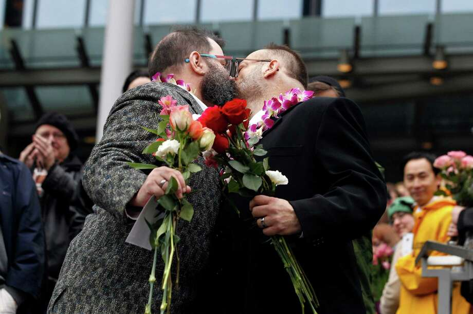 Liam, right, and Richard Sauer-Wooden kiss on the steps of Seattle City Hall after getting married, Sunday, Dec. 9, 2012, in Seattle. Gov. Chris Gregoire signed a voter-approved law legalizing gay marriage Wednesday, Dec. 5 and weddings for gay and lesbian couples began in Washington on Sunday, following the three-day waiting period after marriage licenses were issued earlier in the week. (AP Photo/Elaine Thompson) Photo: Elaine Thompson, STF / AP