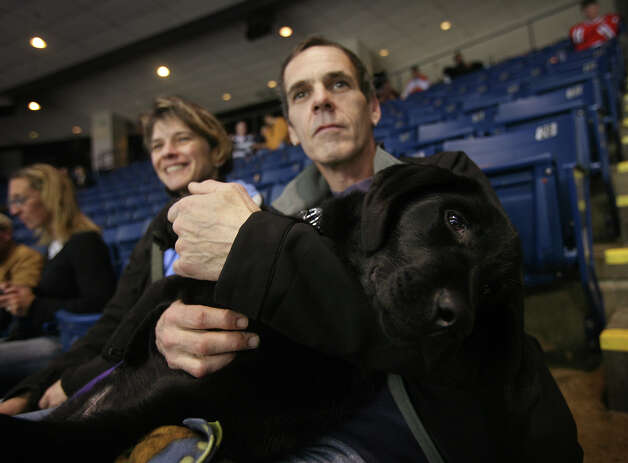 Deb and George Roberts, of Litchfield, and their dog, Jett, watch the Sound Tigers  play Syracuse on Pucks & Paws night at the Webster Bank Arena in Bridgeport on Sunday, December 9, 2012. Proceeds from the event benefit the Bridgeport Animal Hospital. Photo: Brian A. Pounds / Connecticut Post