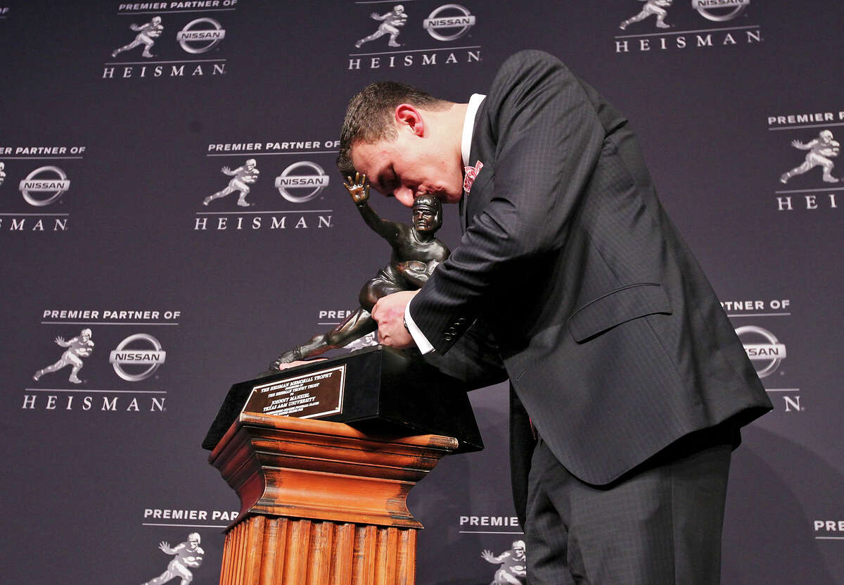 Texas A&M's quarterback Johnny Manziel, the 2012 Heisman Trophy winner, kisses the trophy as he poses for photos during a press conference Saturday Dec. 8, 2012 at the New York Marriott Marquis hotel in New York, New York.