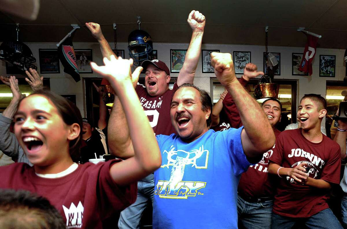 Armando Carranza, middle, and other fans of Texas A&M quarterback Johnny Manziel cheer as Manziel receives the Heisman trophy on television at the Wing King restaurant in Kerrville, Texas, on Saturday night, Dec. 8, 2012. Manziel played high school football for Tivy High School in Kerrville.