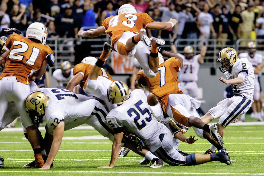 Madison's Josh Meno (top) leaps in the air as O'Connor's Dillon Westall (right) kicks a 37-yard field goal during the fourth quarter of their Class 5A Division I state quarterfinal game with Madison at the Alamodome on Dec. 8, 2012.  O'Connor beat the Mavericks 52-49.  MARVIN PFEIFFER/ mpfeiffer@express-news.net Photo: MARVIN PFEIFFER, Marvin Pfeiffer/ Express-News / Express-News 2012
