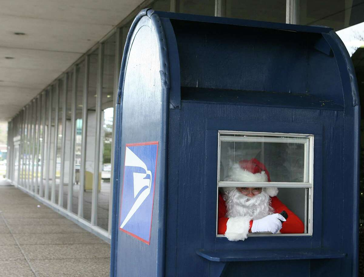 Santa Claus waits inside a giant mail box in front of the Barbra Jordan Post Office to help customers ship mail and packages Sunday, Dec. 9, 2012, in Houston.