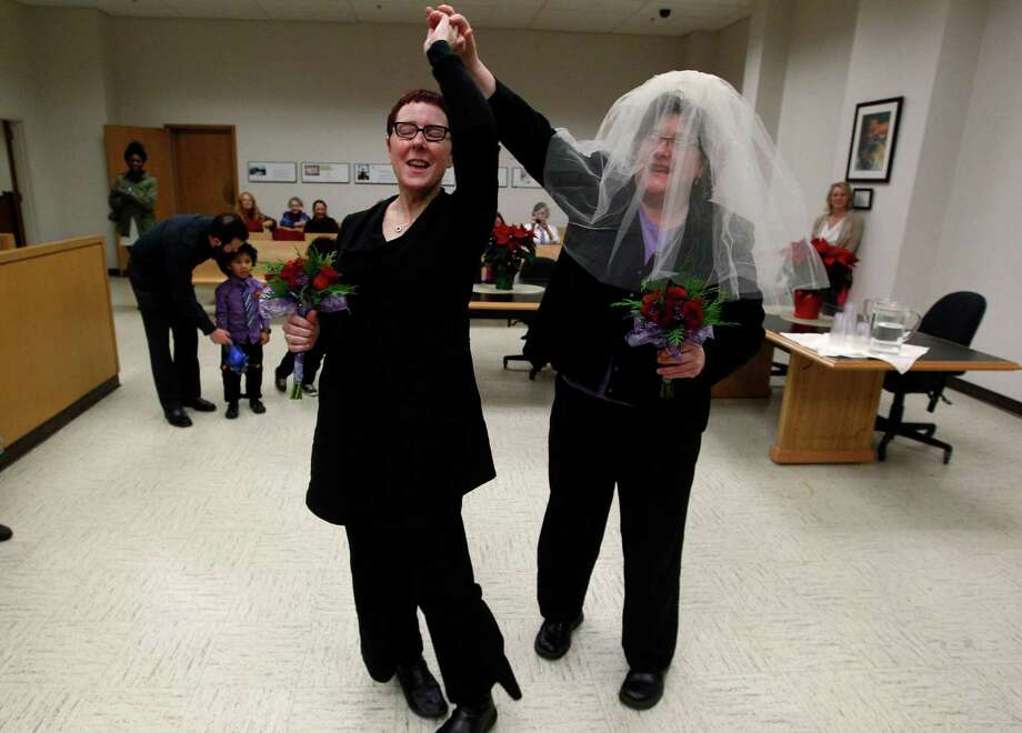 Cynthia Wallace, left, and partner Julie Fein spin a few dance steps as they prepare to take their wedding vows in the early morning hours in the courtroom of Judge Mary Yu in the King County Courthouse Sunday, Dec. 9, 2012, in Seattle. Gov. Chris Gregoire signed a voter-approved law legalizing gay marriage Wednesday, Dec. 5 and weddings for gay and lesbian couples began in Washington on Sunday, following the three-day waiting period after marriage licenses were issued earlier in the week. (AP Photo/Elaine Thompson) Photo: Elaine Thompson, Associated Press / AP
