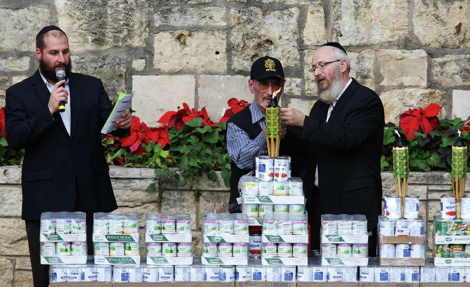 U.S. Army Retired Lt. Col. George Alter, 89 (center), gets help lighting the menorah from Rabbi Chaim Block (right) as Rabbi Yossi Marrus sings prayers during the 15th annual Chanukah on the River celebration. Photo: Jerry Lara, San Antonio Express-News / © 2012 San Antonio Express-News