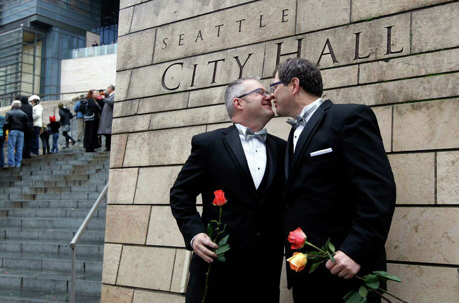 Terry Gilbert, left, kisses his husband Paul Beppler after wedding at Seattle City Hall, becoming among the first gay couples to legally wed in the state, Sunday, Dec. 9, 2012, in Seattle. Gov. Chris Gregoire signed a voter-approved law legalizing gay marriage Dec. 5 and weddings for gay and lesbian couples began in Washington on Sunday, following the three-day waiting period after marriage licenses were issued earlier in the week. (AP Photo/Elaine Thompson) Photo: Elaine Thompson, Associated Press / AP