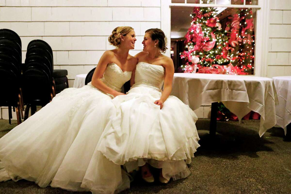 Mary Davidson, 27, left, and her bride Monica Rozgay, 29, take a breather outside in advance of their official midnight ceremony at The Seattle Yacht Club early Sunday Dec. 9, 2012. Rozgay and Davidson, of Seattle, were one of the first couples to wed following the passage of Referendum 74, which approved a bill legalizing same-sex marriage in the state of Washington. (AP Photo/The Seattle Times, Bettina Hansen)